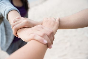 Three people join hands together on white sand beach background. Friendship Day, collaboration of business and education teamwork concept.